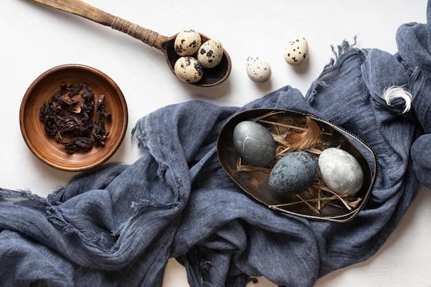 Lay piatto di uova di pasqua con cucchiaio di legno e tessile