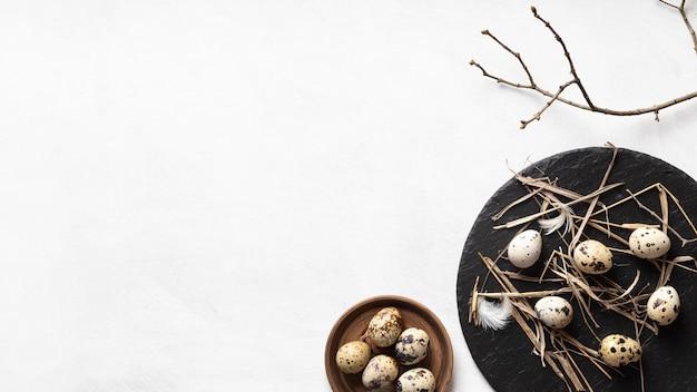 Lay piatto di uova di pasqua sul piatto di legno e ardesia con spazio di copia