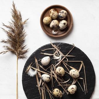 Lay piatto di uova di pasqua sul piatto di legno e ardesia