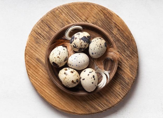 Lay piatto di uova di pasqua sul piatto di legno con piume