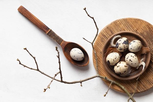 Lay piatto di uova di pasqua sul piatto di legno con cucchiaio e ramoscello