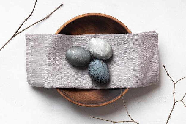Lay piatto di uova di pasqua sul piatto di legno con tessili