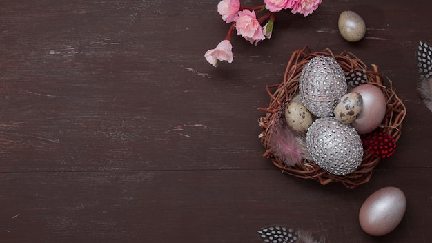 Плоское пасхальное гнездо и яйца на коричневом фоне с розовыми цветами копией пространства