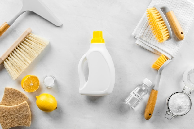 Flat lay of eco-friendly cleaning products collection with brushes and lemon
