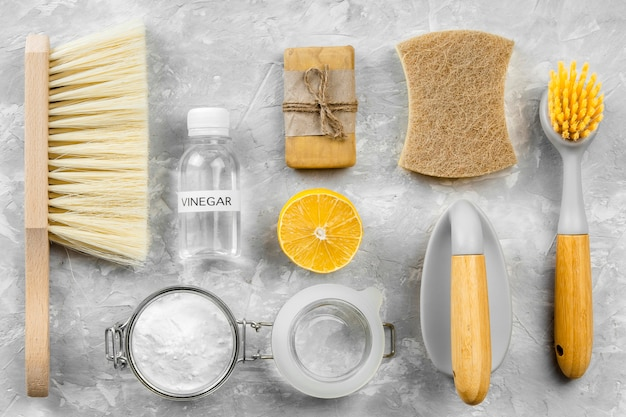 Flat lay of eco-friendly cleaning products with brushes and lemon