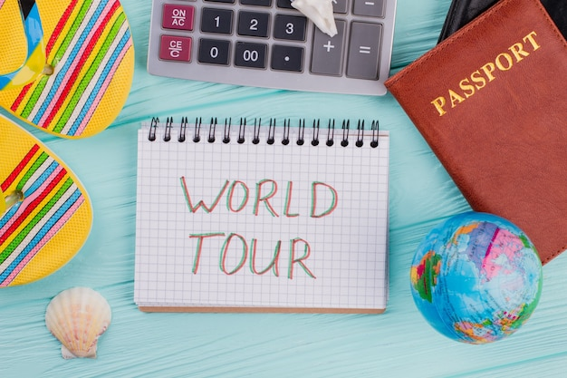 Flat lay economic and travel composition. calculator, notebook, glasses, globe and passport on blue pink pastel background. from top view.