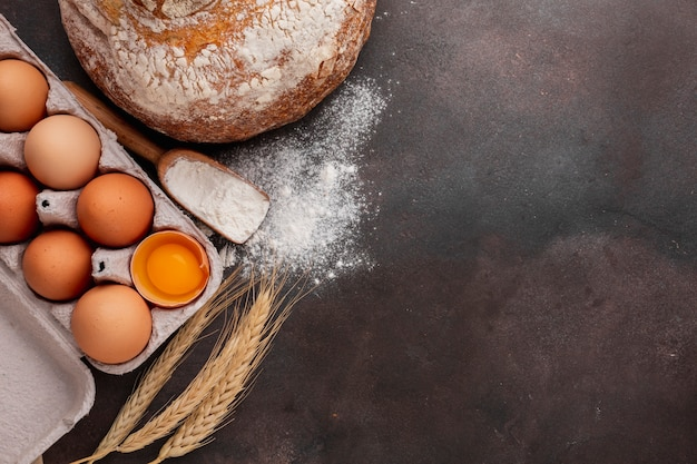 Flat lay of egg carton with bread and flour