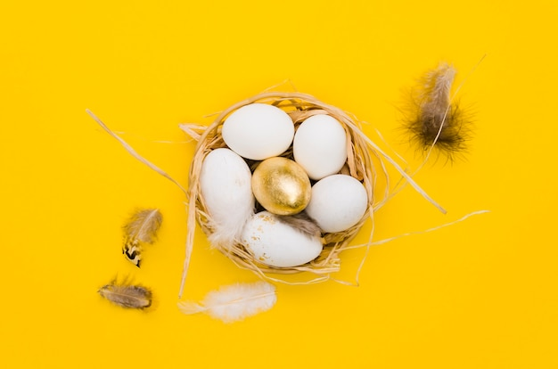 Flat lay of eggs in basket for easter with gold paint and feathers
