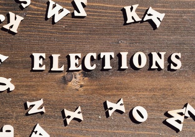 Flat lay elections lettering on wooden background
