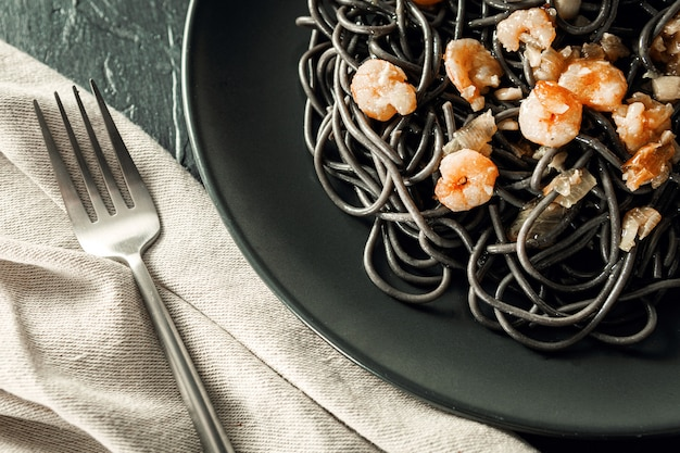 Flat lay of elegant black plate of pasta with sepia ink and prawns next to a silver fork and linen napkin with black textured background