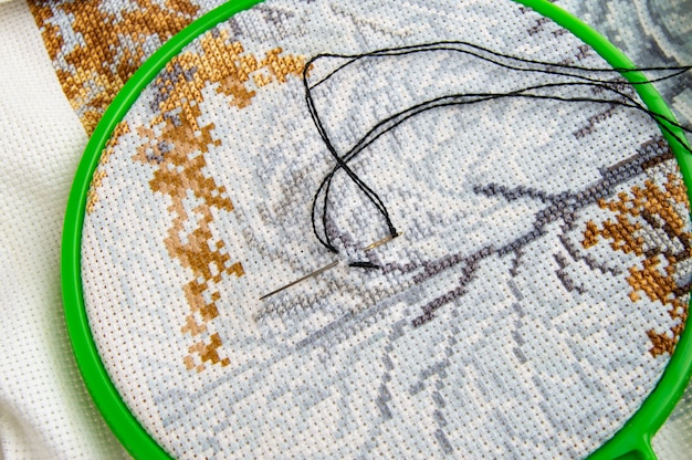 Flat lay embroidery hoop with canvas and bright sewing thread and embroidery needle