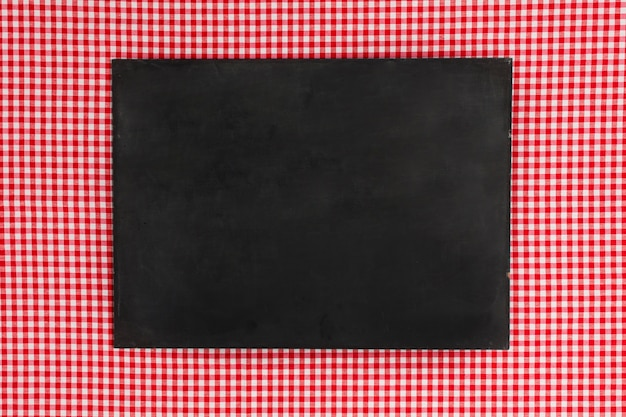 Flat lay empty blackboard on red cloth