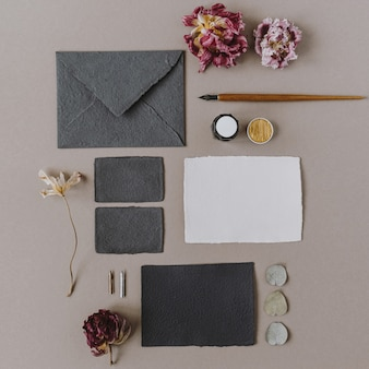 Flat lay empty blank paper card, envelope, pen, flower buds on beige. flat lay, top view
