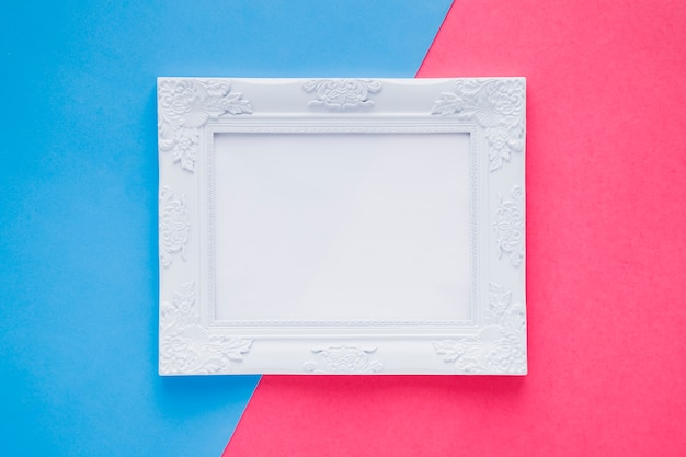 Flat lay empty frame on bicolor background