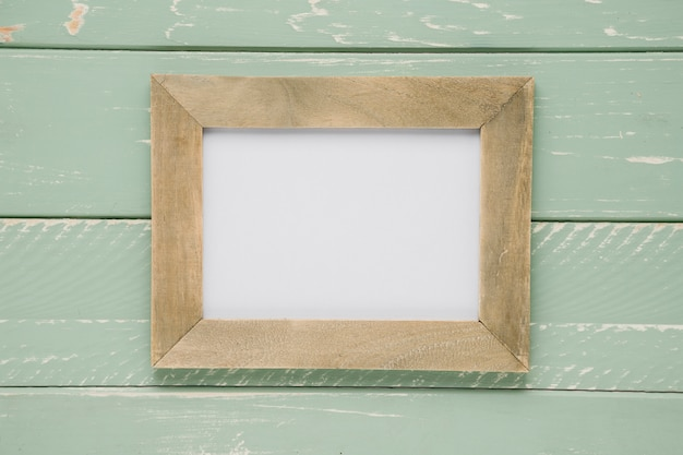 Flat lay empty frame on light wooden background