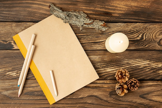 Flat lay empty notebook next to pine cones