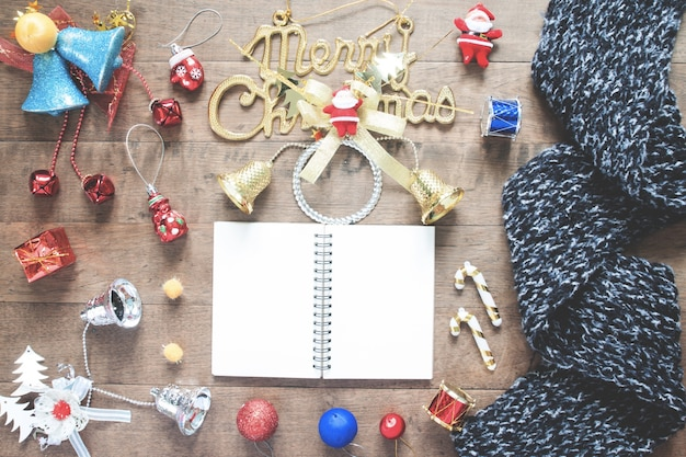 Flat lay of empty notebook, winter scarf and christmas decoration items on wood background, vintage filter