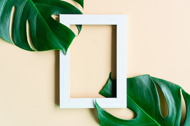 Flat lay of empty photo frame and green leaves on beige color background. top view and copy space