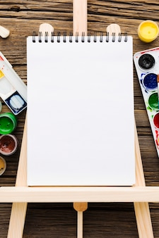 Flat lay empty white notepad and paint
