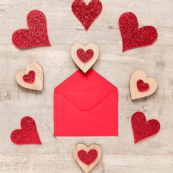 Flat lay of envelope with hearts on wooden background