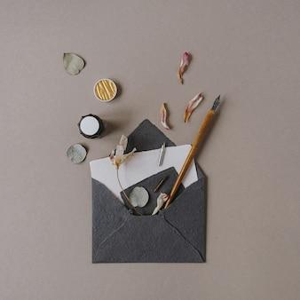 招待状、ペン、ベージュの花びらが付いた平置き封筒。結婚式の招待状。フラットレイ、上面図