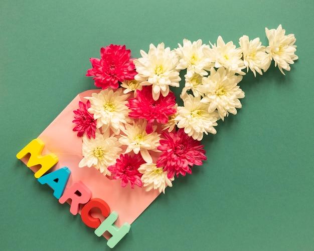 Disposizione piatta della busta con mese e fiori per la festa della donna
