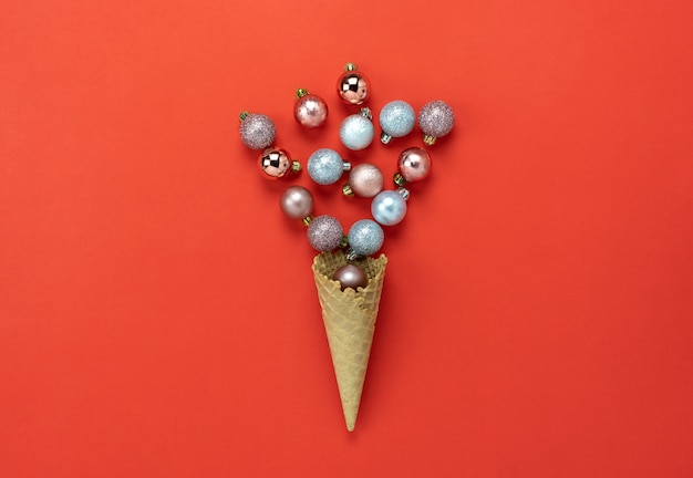 Flat lay essential difference objects baubles & ice cream cone laying on red paper backgro