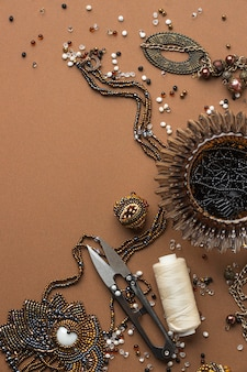 Flat lay of essentials for bead working with scissors and copy space