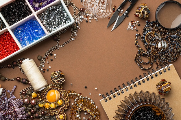 Flat lay of essentials for bead working with scissors and notebook