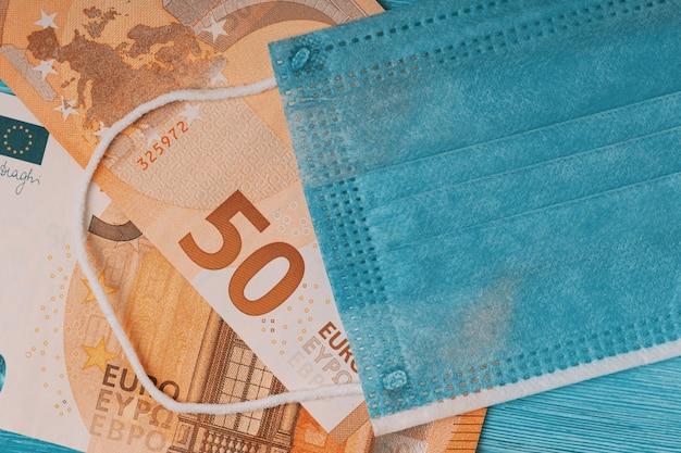 Flat lay of face mask and euro banknotes