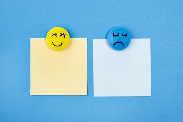 Disposizione piatta di facce con emozioni e note adesive per il lunedì blu