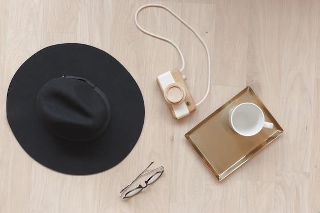 レトロなスタイルのフラットレイファッションアクセサリー。木製のカメラ、メガネ、帽子、カップとビンテージスタイルの構成