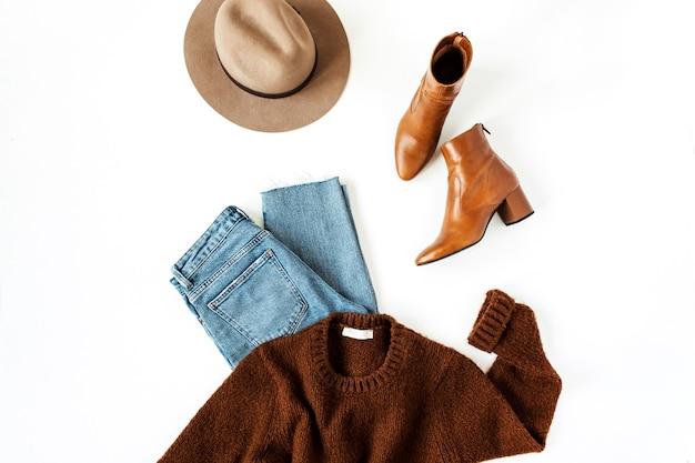 여성 현대 의류 및 액세서리 화이트 플랫 누워 패션 콜라주. 갈색 모직 풀오버, 신발, 모자, 청바지