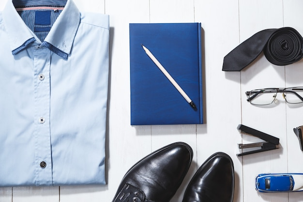 実業家のアクセサリーのフラットレイファッションセット、白い木製の背景の上面図