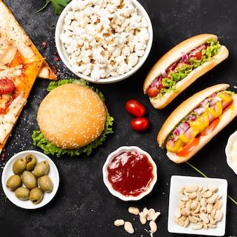 Piatto disteso di fast food sul tavolo nero Foto Gratuite