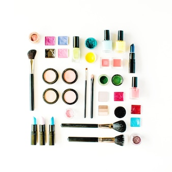 Flat lay female cosmetics collage with lipstick, brush on white