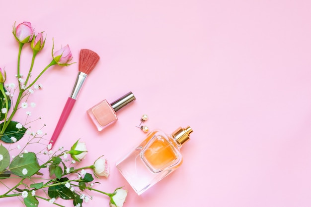 Flat lay of female cosmetics products and accessories. a bottle of perfume, nude nail polish, pearl earings and roses on pink background. copy space.