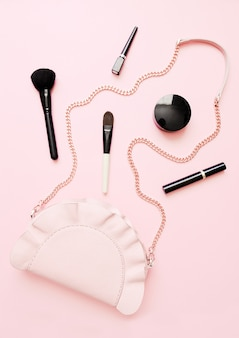Flat lay of female fashion accessories, makeup products and handbag on pastel color background