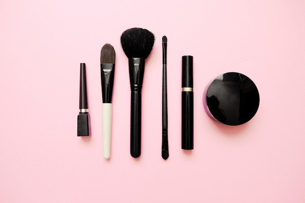 Flat lay of female fashion makeup products on pastel color background