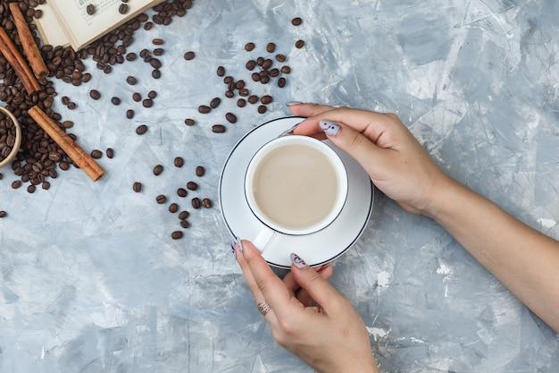 コーヒー豆、シナモンスティック、灰色の石膏の背景の本とコーヒーのカップを保持している平らな女性の手。水平