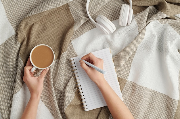 Flat lay of female hands with pen over blank page of notebook and cup of fresh cappuccino making working notes or plan at break