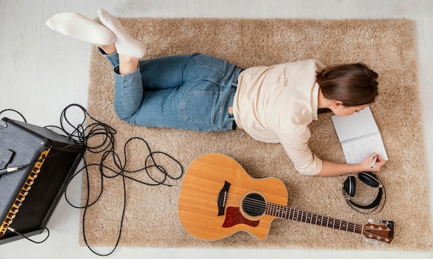 Piatto di laici musicista a casa a scrivere canzoni con cuffie e chitarra acustica