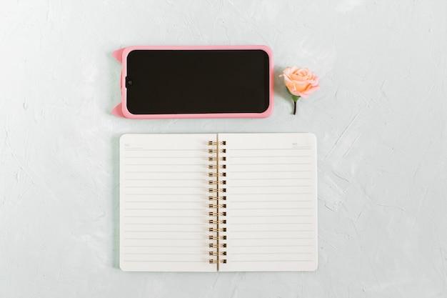 フラットレイフェミニンなホームオフィスデスク。灰色の背景にメモ帳、電話、花のモックアップ。