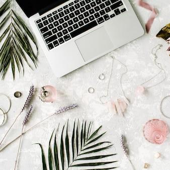노트북, 프로테우스 꽃, 목걸이, 종려 나무 가지 및 액세서리가있는 평평하고 여성스러운 홈 오피스 작업 공간