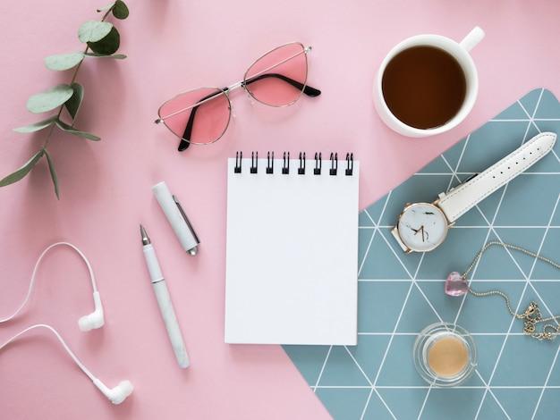 Плоская планировка женский макет тетради с делами. чай, канцелярские товары и косметические принадлежности на розовом фоне.