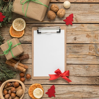 Flat lay festive christmas table arrangement with empty clipboard