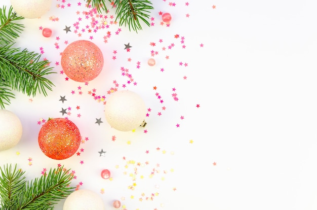 Flat lay fir branches with christmas decorations and confetti on a white background