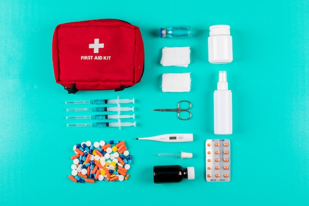 Flat lay first aid kit with pills, thermometer, spray, pills and bandage on cyan blue background. horizontal