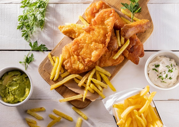 Flat lay of fish and chips on chopping board with sauce