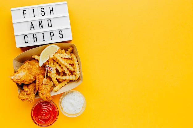 Flat lay of fish and chips with sauce and light box